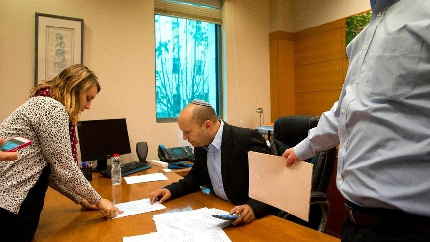 Naftali Bennett, leader of the Jewish Home party, works in his office before an interview to The Associated Press in Jerusalem, Monday, Feb. 16, 2015. With Benjamin Netanyahu under fire internationally for his hardline policies, a key partner of Israeli prime minister is standing firmly behind him ahead of the March parliamentary elections heralding what could be an even tougher stance toward the Palestinians if they sit together in the next government. (AP Photo/Tsafrir Abayov)
