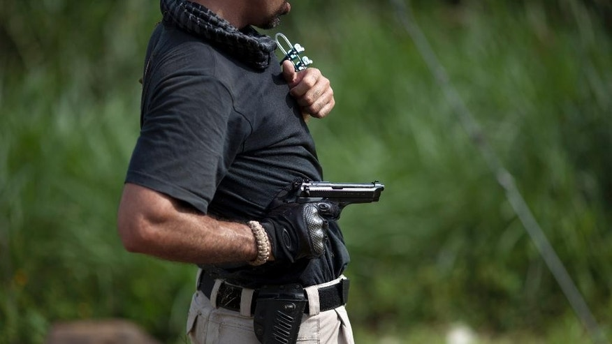 In this Sept. 17, 2014 photo, Julio Delgado demonstrates a tactical gun position, during a training session for fellow bodyguards, in Maracay, Venezuela. Delgado, who directs security for the family of a powerful automobile importer, is among the private bodyguards who are becoming more common, and increasingly targeted, as Venezuela is hit by an epidemic of crime. (AP Photo/Ariana Cubillos)
