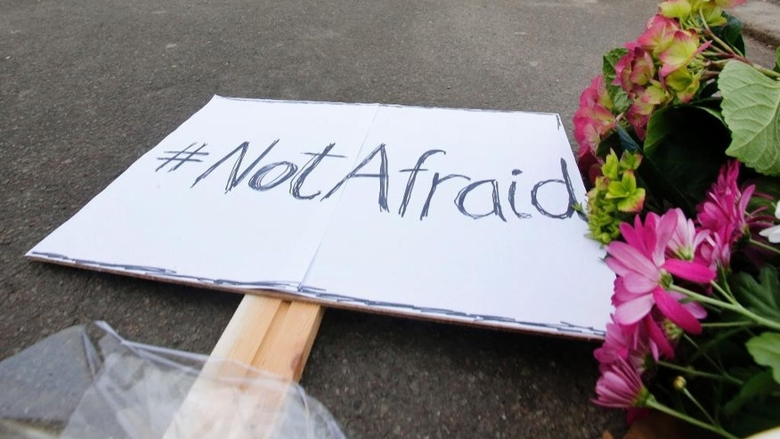 "A sign declaring ""Not Afraid"" placed with flower tributes near the cultural club where one person was killed in Copenhagen, Denmark, Sunday, Feb. 15, 2015.  The alleged shooter was later killed by police who believe he also shot another person at a synagogue. (AP Photo/Michael Probst)"