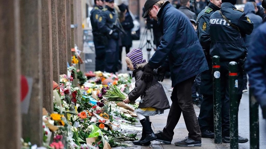 People laying flowers outside a synagogue where an attack took place, in Copenhagen, Sunday, Feb. 15, 2015. Danish police shot and killed a man early Sunday suspected of carrying out shooting attacks at a free speech event and then at a Copenhagen synagogue, killing a Danish documentary filmmaker and a member of the Scandinavian country's Jewish community. Five police officers were also wounded in the attacks. (AP Photo/Polfoto, Jens Dresling)  DENMARK OUT