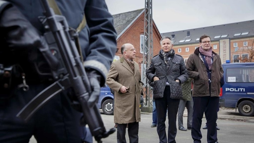French Minister of Interior Bernard Cazeneuve, left, and French Ambassador to Denmark Francois Zimeray, centre, at the crime scene in Copenhagen, Sunday, Feb. 15, 2015. Danish police shot and killed a man early Sunday suspected of carrying out shooting attacks at a free speech event and then at a Copenhagen synagogue, killing two men, including a member of Denmark's Jewish community and wounding five police officers in the attacks. (AP Photo/Polfoto, Mads Nissen) DENMARK OUT