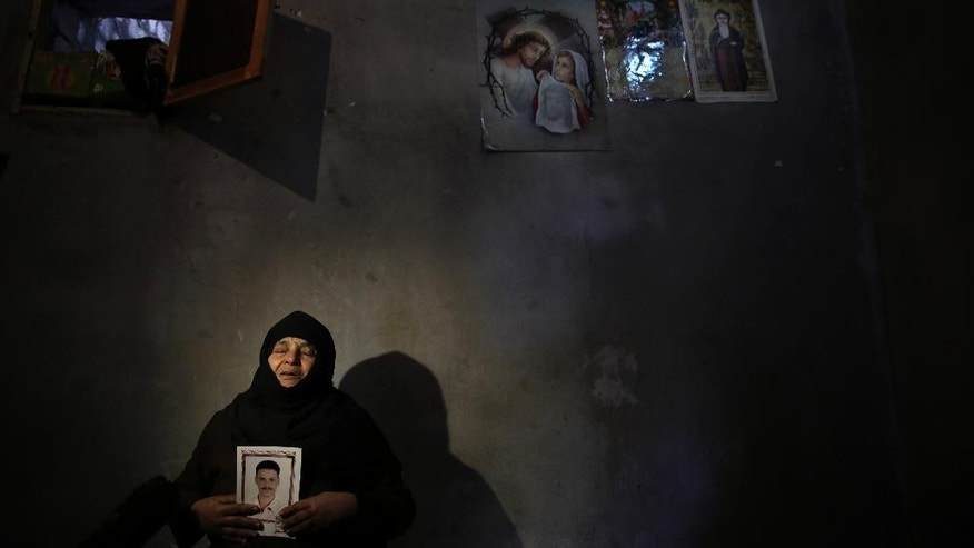 In this Saturday, Feb. 14, 2015 photo, Ibtassal Lami, mother of abducted Coptic Christian Samuel Walham, one of 21 Coptic Egyptian men seized by Islamic State militants in the central city of Sirte, Libya more than a month ago, holds his picture as she weeps at their home in the village of el-Aour near Minya, 220 kilometers (135 miles) south of Cairo, Egypt. A video purporting to show the mass beheading of Coptic Christian hostages was released Sunday, Feb. 15, 2015, by militants in Libya affiliated with the Islamic State group. (AP Photo/Hassan Ammar)