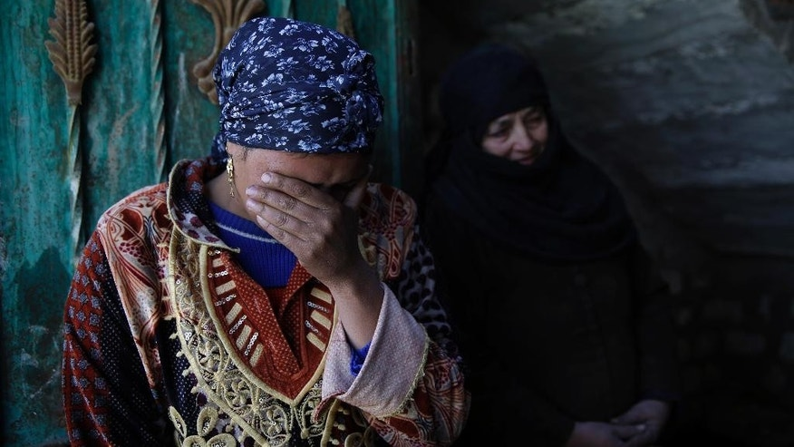 In this Saturday, Feb. 14, 2015 photo, family relatives of abducted Coptic Christian Samuel Walham, one of 21 Coptic Egyptian men seized by Islamic State militants in the central city of Sirte, Libya, more than a month ago, weep outside their home in the village of el-Aour, near Minya, 220 kilometers (135 miles) south of Cairo, Egypt. A video purporting to show the mass beheading of Coptic Christian hostages was released Sunday, Feb. 15, 2015, by militants in Libya affiliated with the Islamic State group. (AP Photo/Hassan Ammar)