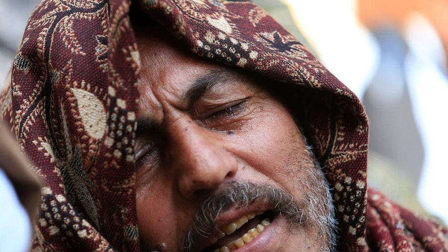 A man mourns for the Egyptian Coptic Christians captured in Libya and killed by militants affiliated with the Islamic State group, outside of the Virgin Mary church in the village of el-Aour, near Minya, 220 kilometers (135 miles) south of Cairo, Egypt, Monday, Feb. 16, 2015. Egyptian warplanes struck Islamic State targets in Libya on Monday in swift retribution for the extremists' beheading of a group of Egyptian Christian hostages on a beach, shown in a grisly online video released hours earlier. (AP Photo/Hassan Ammar)
