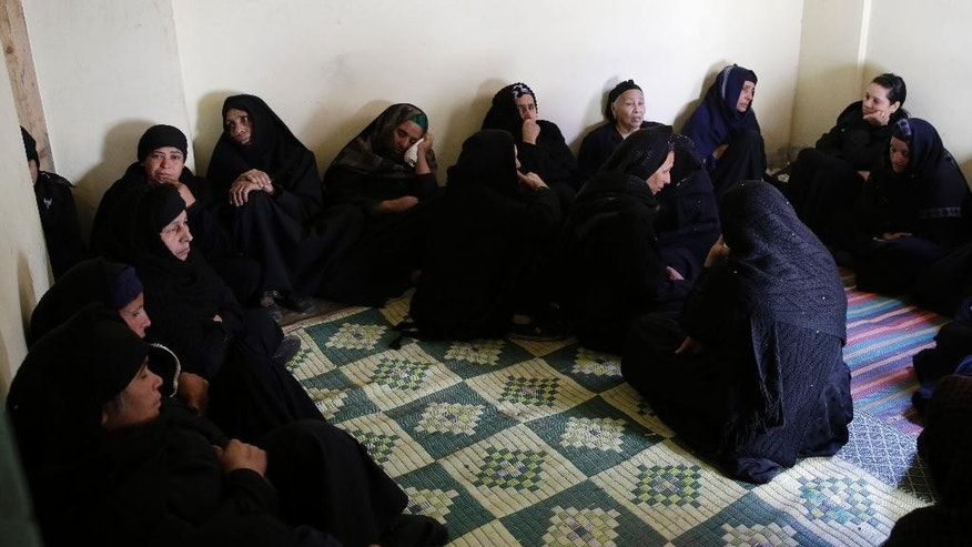 Women mourn over Egyptian Coptic Christians who were captured in Libya and killed by militants affiliated with the Islamic State group, inside the Virgin Mary Church in the village of el-Aour, near Minya, 220 kilometers (135 miles) south of Cairo, Egypt, Monday, Feb. 16, 2015. Egyptian warplanes struck Islamic State targets in Libya on Monday in swift retribution for the extremists' beheading of a group of Egyptian Christian hostages on a beach, shown in a grisly online video released hours earlier. (AP Photo/Hassan Ammar)