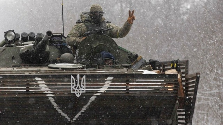 Feb. 16, 2015: An Ukrainian soldier strikes a V-Victory sign driving on his vehicle on the road between the towns of Debaltseve and Artemivsk, Ukraine. (AP Photo/Petr David Josek)