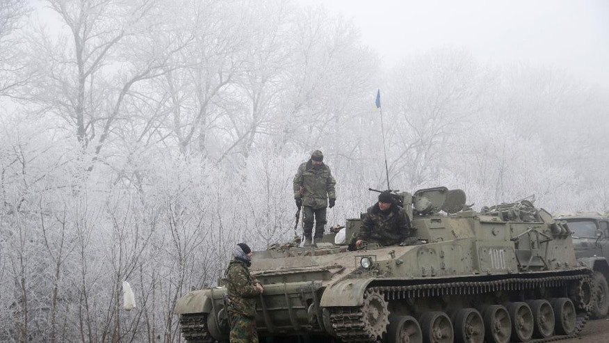 Damaged armored vehicle lies on the road near the village of Luganske, Ukraine, Sunday, Feb. 15, 2015. International attention will be focused in the coming days on the strategic railway hub of Debaltseve, where Ukrainian government forces have for weeks been fending off severe onslaughts from pro-Russian separatists. A cease-fire was declared in eastern Ukraine, kindling slender hopes of a reprieve from a conflict that has claimed more than 5,300 lives. (AP Photo/Petr David Josek)