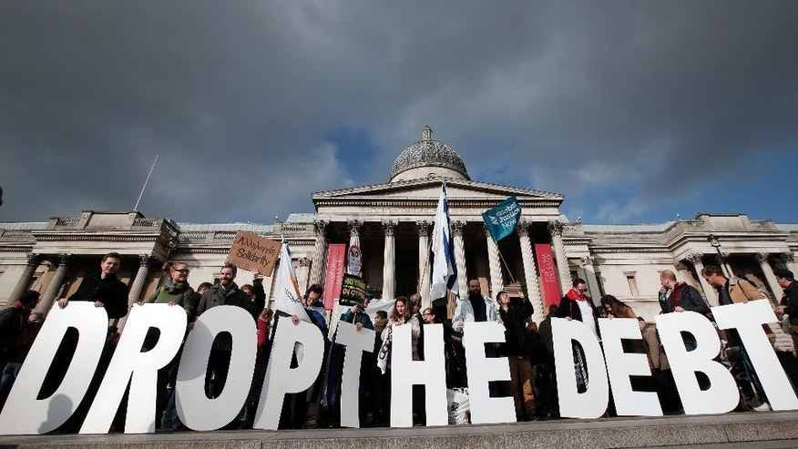 "Protesters hold placards during a rally to show solidarity with Greece in central London, Sunday, Feb. 15, 2015. Hundreds of protesters gathered in support of the new government and the anti-austerity movement in Greece. Greece's new left-wing government is pressing for a short-term ""bridge"" agreement with eurozone lenders and a longer-term debt relief deal later this year. (AP Photo/Lefteris Pitarakis)"