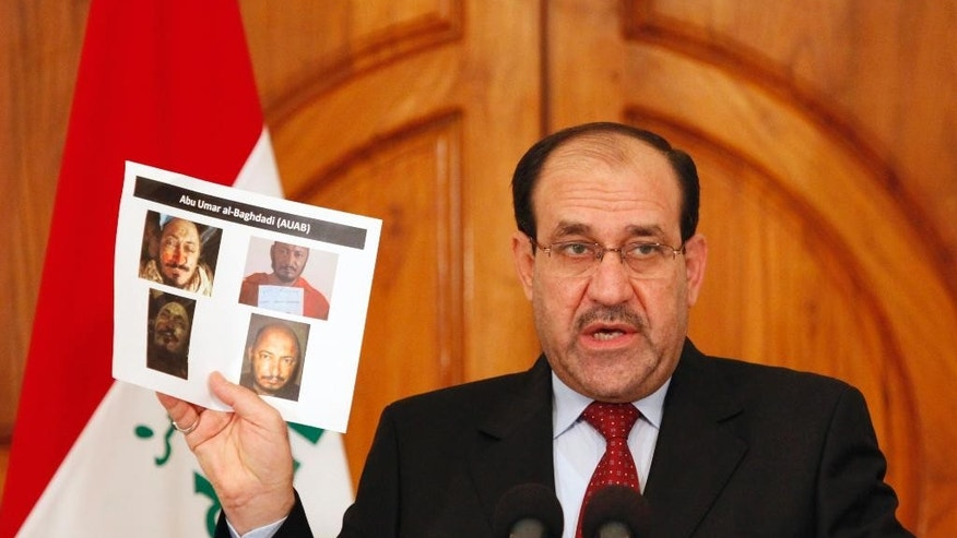 FILE - In this Monday, April 19, 2010 file photo, Iraq's Prime Minister Nouri al-Maliki holds a paper displaying photographs of a man the Iraqi government claims to be al-Qaida leader Abu Omar al-Baghdadi at a news conference in Baghdad, Iraq. U.S. and Iraqi forces killed the two top al-Qaida in Iraq leaders on April 18, 2010, allowing Abu Bakr al-Baghdadi to become the leader of a terror group weakened by a concerted campaign aimed at ending a Sunni insurgency in the country.(AP Photo/Hadi Mizban, File)