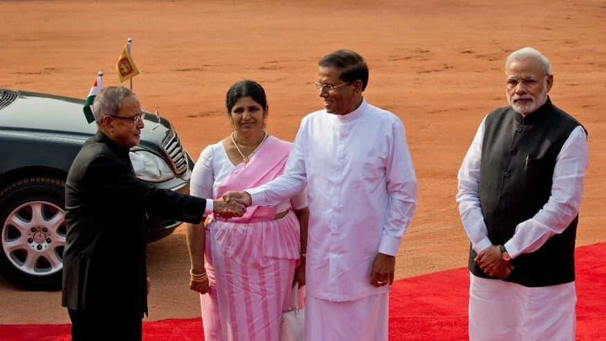 Indian President Pranab Mukherjee, left, shakes hands with Sri Lanka's President Maithripala Sirisena, second right, as his wife Jayanthi Sirisena, second left, and Indian Prime Minister Narendra Modi watch during a ceremonial reception at the Indian presidential palace in New Delhi, India, Monday, Feb. 16, 2015. Sri Lanka's new leader is underlining India's importance as a regional ally by making it his first official foreign destination as president, following years of uneasy relations with New Delhi and international pressure to speed up post-civil war reconciliation efforts at home. (AP Photo/Manish Swarup)