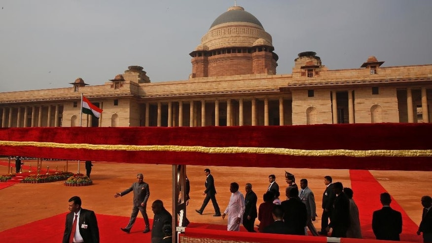 Sri Lanka's President Maithripala Sirisena, center in white, walks on the red carpet with Indian President Pranab Mukherjee, center wearing spectacles, after inspecting a guard of honor during a ceremonial reception at the Indian Presidential Palace in New Delhi, India, Monday, Feb. 16, 2015. Sri Lanka's new leader is underlining India's importance as a regional ally by making it his first official foreign destination as president, following years of uneasy relations with New Delhi and international pressure to speed up post-civil war reconciliation efforts at home. (AP Photo/Manish Swarup)