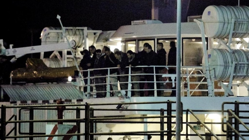 Men stand on the deck of the San Gwann Maltese ship used to repatriate Italians from Libya, as it arrives at the southern Italian port of Augusta, early Monday morning, Feb. 16, 2015. Italy repatriated by sea its personnel from its Tripoli embassy and advised other Italians, many of whom work in oil or construction businesses, to leave Libya. (AP Photo/Francesco Malavolta)