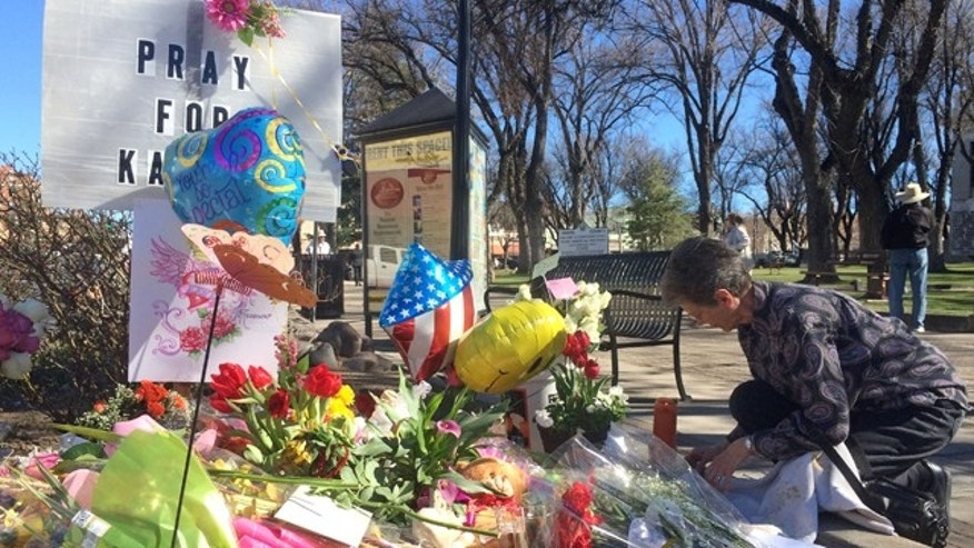 Feb. 12, 2015: An unidentified woman kneels near a makeshift memorial for Kayla Mueller in Prescott, Ariz. (AP)