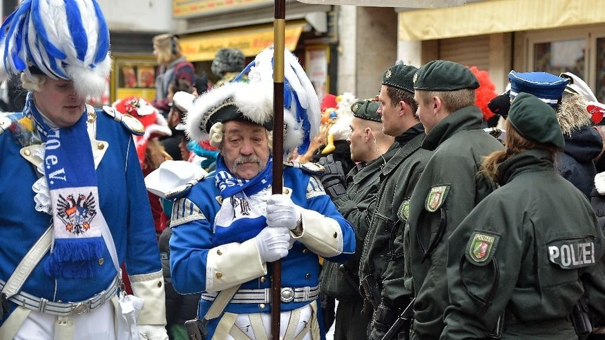 Police secure the traditional carnival parade in Cologne, western Germany, Monday, Feb. 16, 2015. The foolish street spectacle in Cologne, watched by hundreds of thousands of people ,is one of the highlights in Germany's carnival season on Rose Monday. A parade in Braunschweig, Germany  was canceled yesterday because of a terror threat. (AP Photo/Martin Meissner)