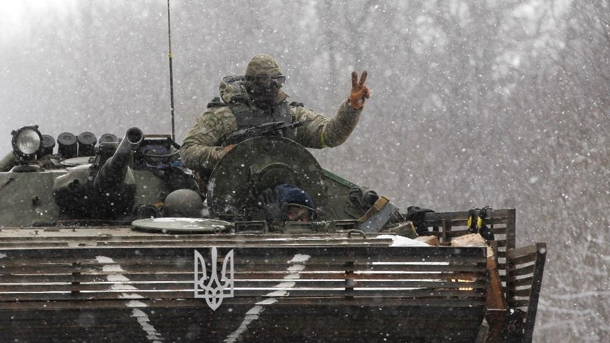 An Ukrainian soldier strikes a V-Victory sign driving on his vehicle on the road between the towns of Debaltseve and Artemivsk, Ukraine, Monday, Feb. 16, 2015. The Ukrainian government and Russia-backed rebels accused each other Monday of violating a cease-fire in eastern Ukraine, a day before the parties are due to start withdrawing heavy weaponry under a recently brokered deal. The cease-fire, which went into effect on Sunday, had raised cautious hopes for an end to the 10-month-old conflict, which has already claimed more than 5,300 lives. (AP Photo/Petr David Josek)