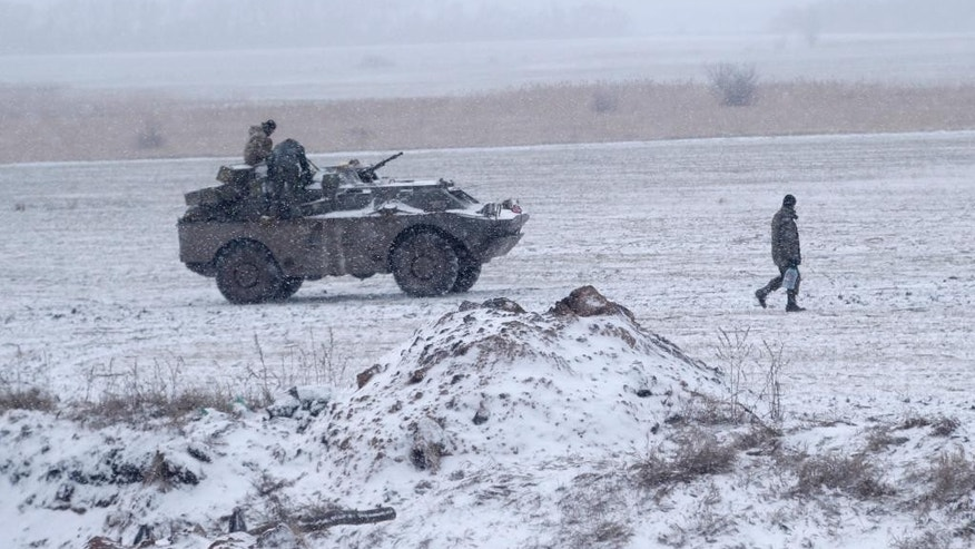An Ukrainian soldier carries water past a vehicle standing on a field near the road between the towns of Debaltseve and Artemivsk, Ukraine, Monday, Feb. 16, 2015. The Ukrainian government and Russia-backed rebels accused each other Monday of violating a cease-fire in eastern Ukraine, a day before the parties are due to start withdrawing heavy weaponry under a recently brokered deal. The cease-fire, which went into effect on Sunday, had raised cautious hopes for an end to the 10-month-old conflict, which has already claimed more than 5,300 lives. (AP Photo/Petr David Josek)