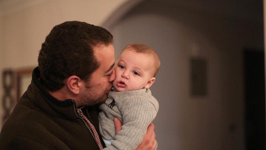 Al-Jazeera English journalist Baher Mohammed kisses his 6 month-old son Haroon, who was born while he was in prison, during an interview with the Associated Press at his home in 6 October city, a suburb southwest of Cairo, Egypt, Tuesday, Feb. 17, 2015. Mohammed, one of three Al-Jazeera English journalists released after over a year in Egyptian prison says he is optimistic he would be exonerated from terrorism-related charges during his retrial which begins next week. (AP Photo/Mosa'ab Elshamy)