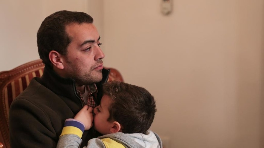 Al-Jazeera English journalist Baher Mohammed holds his 6 month-old son Haroon, who was born while he was in prison, during an interview with the Associated Press at his home in 6 October city, a suburb southwest of Cairo, Egypt, Tuesday, Feb. 17, 2015. Mohammed, one of three Al-Jazeera English journalists released after over a year in Egyptian prison says he is optimistic he would be exonerated from terrorism-related charges during his retrial which begins next week. (AP Photo/Mosa'ab Elshamy)