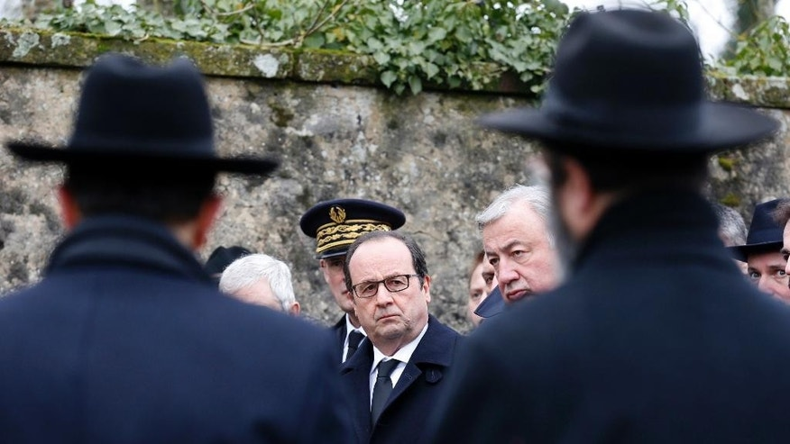 French President Francois Hollande, center, and Senate President Gerard Larcher , right, attend a ceremony during a visit at the Sarre-Union Jewish cemetery, eastern France, Tuesday Feb. 17, 2015. Hollande spoke Tuesday in Sarre-Union, where 250 Jewish graves were desecrated over the weekend. Hollande noted anti-Semitism and acts against Muslims are both on the rise in France, notably after the attacks last month in Paris that left 20 people dead, including the three gunmen. The president called on French Jews to remain in France and not follow the Israeli prime minister's call for a mass immigration of European Jews. (AP Photo/Vincent Kessler/Pool)