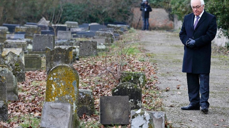 Israeli ambassador to France Yossi Gal stands near desecrated tombstones during a ceremony at the Sarre-Union Jewish cemetery, eastern France, Tuesday Feb. 17, 2015.  Hollande spoke Tuesday in Sarre-Union, where 250 Jewish graves were desecrated over the weekend. Hollande noted anti-Semitism and acts against Muslims are both on the rise in France, notably after the attacks last month in Paris that left 20 people dead, including the three gunmen. The president called on French Jews to remain in France and not follow the Israeli prime minister's call for a mass immigration of European Jews. (AP Photo/Vincent Kessler/Pool)