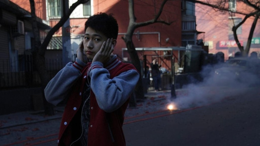A man covers his ears as he walks past firecrackers set off by people on a street in Beijing Wednesday, Feb. 18, 2015. Setting off fireworks to celebrate Chinese New Year may be a centuries-old tradition, but the country's authorities are urging people to light fewer of them this week as cities fight a losing battle against relentless, toxic air pollution. (AP Photo/Andy Wong)