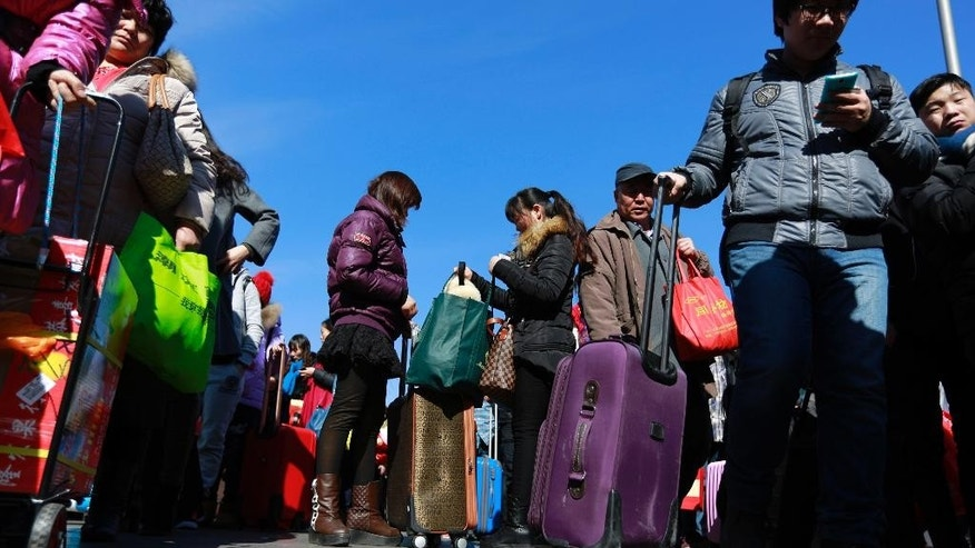 Chinese traveler queue up at the main entrance to the Beijing railway station in Beijing, Tuesday, Feb. 17, 2015. Millions of Chinese are traveling to their hometowns to celebrate the Lunar New Year on Feb. 19 this year which marks the Year of the Sheep on the Chinese zodiac. (AP Photo/Andy Wong)