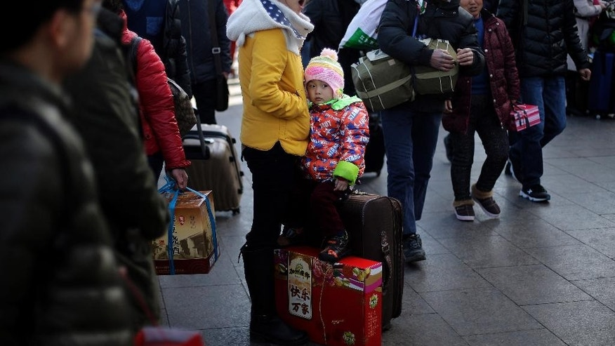 A woman yawns next to her child as passengers arrive at the main entrance of the Beijing railway station to catch their trains in Beijing, China Tuesday, Feb. 17, 2015. Millions of Chinese are traveling to their hometowns to celebrate the Lunar New Year on Feb. 19 this year which marks the Year of the Sheep on the Chinese zodiac. (AP Photo/Andy Wong)