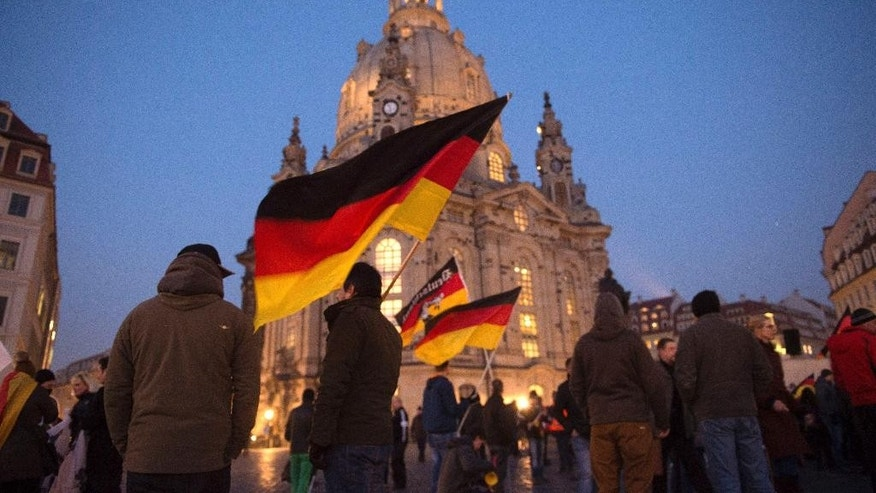 The Monday, Feb. 16, 2015 photo shows protestors of the anti-Islamic Pegida (Patriotic Europeans against the Islamization of the West) alliance gather at a demonstration in front of the Church of our Lady and hold up German flags in Dresden, Germany. (AP Photo/dpa, Sebastian Kahnert)