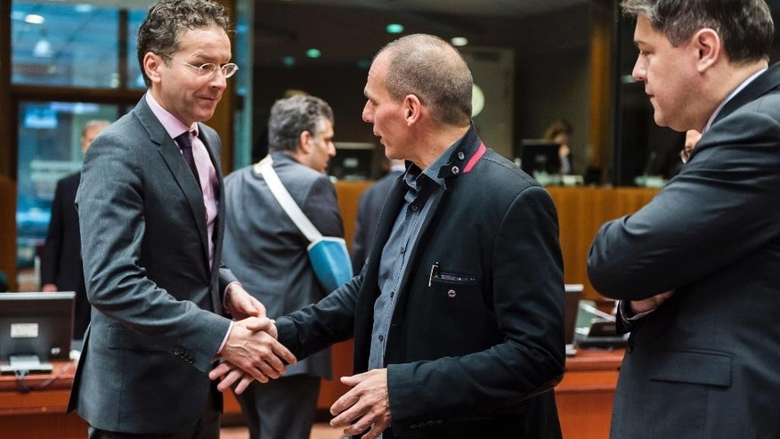 Greece's Finance Minister Yanis Varoufakis, center, greets Dutch Finance Minister Jeroen Dijsselbloem, left, as Croatian Finance Minister Boris Lalovac looks on during a meeting of EU finance ministers at the EU Council building in Brussels Tuesday, Feb. 17, 2015. Greek shares led a European retreat Tuesday as investors reacted negatively to the breakdown in talks between Greece and its creditors in the 19-nation eurozone over the country's attempt to renegotiate its financial bailout. (AP Photo/Geert Vanden Wijngaert)