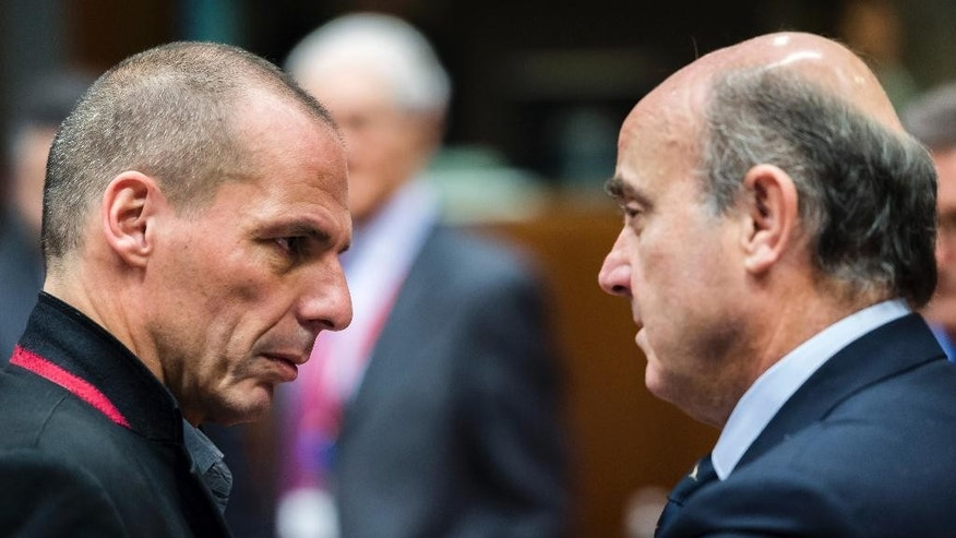 Greece's Finance Minister Yanis Varoufakis, left, talks with Spanish Economy Minister Luis de Guindos during a meeting of EU finance ministers at the EU Council building in Brussels Tuesday, Feb. 17, 2015. Greek shares led a European retreat Tuesday as investors reacted negatively to the breakdown in talks between Greece and its creditors in the 19-nation eurozone over the country's attempt to renegotiate its financial bailout. (AP Photo/Geert Vanden Wijngaert)