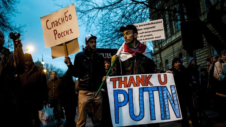 """Sympathizers of Russian President Vladimir Putin demonstrate to express their support for Putin in front of the Russian Embassy in Budapest during the one-day working visit of Putin in the Hungarian capital Tuesday, Feb. 17, 2015. The inscription at left reads """"Thank you, Russia"""". (AP Photo/MTI, Janos Marjai)"""