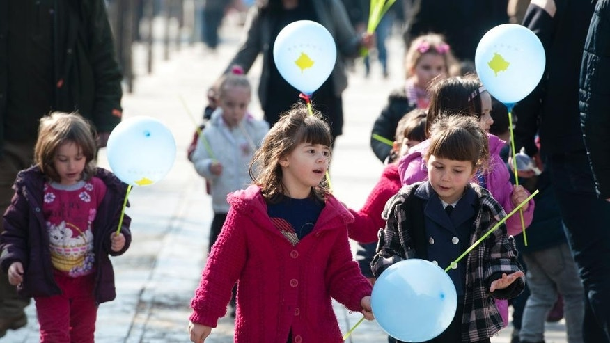 Kosovo Albanian children carry balloons bearing the Kosovo flag as they walk through the Mother Teresa square in the Kosovo capital of Pristina on Monday, Feb. 16, 2015. Festivities marking the 7th anniversary of Kosovo's Independence from Serbia have been kept low-key amid growing social discontent, in Europe's youngest, poorest and most isolated country. (AP Photo)