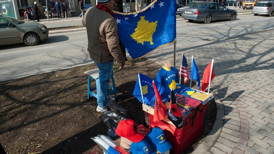 A street vendor displays Kosovo and Albanian flags along with other paraphernalia for sale in the Kosovo capital of Pristina on Monday, Feb. 16, 2015. Festivities marking the 7th anniversary of Kosovo's Independence from Serbia have been kept low-key amid growing social discontent, in Europe's youngest, poorest and most isolated country.(AP Photo)