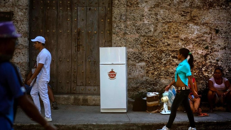 Two women sit on a sidewalk next to their refrigerator and other belongings as they wait for a moving truck to transport them to their new residence, in Havana, Cuba, Tuesday, Feb. 17, 2015. A more relaxed and hopeful atmosphere is evident in Cuba as a result of President Raul Castroís modest reforms and afte the agreement by Cuba and the U.S. to move toward a more normal relationship. (AP Photo/Ramon Espinosa)