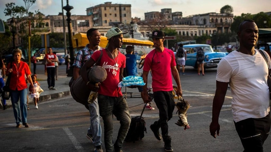 Three young men cross the street carrying a bottle of rum, a cake, a drum and a rooster, on their way to a religious ceremony, in Havana, Cuba, Tuesday, Feb. 17, 2015.  A more relaxed and hopeful atmosphere is evident in Cuba as a result of President Raul Castroís modest reforms and afte the agreement by Cuba and the U.S. to move toward a more normal relationship. (AP Photo/Ramon Espinosa)