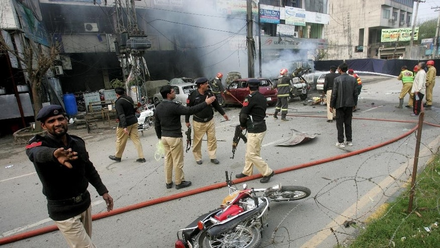 Pakistani police officers cordon off the site of a bombing in Lahore, Pakistan, Tuesday, Feb. 17, 2015. An apparent suicide bombing killed many people outside a police complex in eastern Pakistan on Tuesday, officials said, in a rare attack on the relatively peaceful city of Lahore. (AP Photo/K.M. Chaudary)