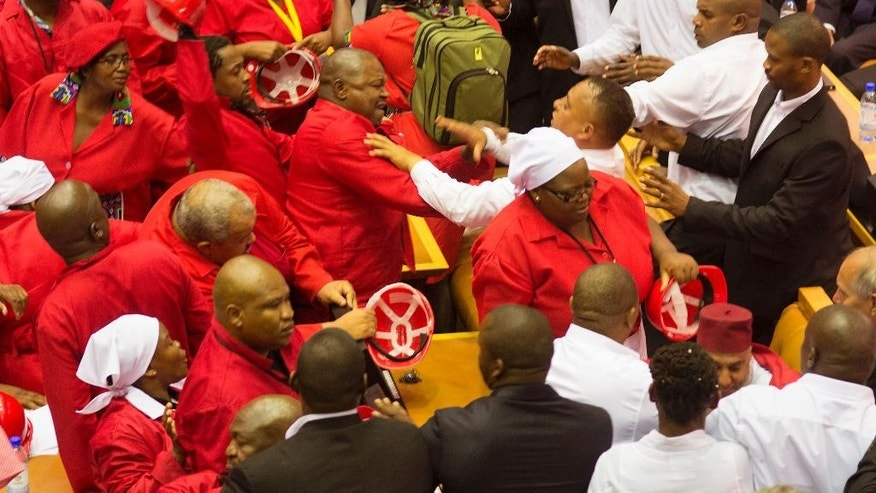 Feb. 12, 2015: South African Economic Freedom Fighters, EFF,  disrupted the official opening session inside Parliament with Security personnel dresses in white shirts try and stop the violence  in Cape Town, South Africa. (AP)