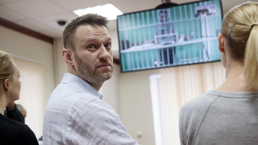 Russian opposition activist and anti-corruption crusader Alexei Navalny, center, his wife Yulia, left, and his brother Oleg's wife Victoria attend a video call with Oleg, shown on a TV screen, at a court in Moscow, Russia, Tuesday, Feb. 17, 2015. Oleg Navalny was convicted on Dec. 30, 2014 and sentenced for three and a half years. Alexei Navalny was also convicted and sentenced to the same prison term, but it was suspended. (AP Photo/Pavel Golovkin)