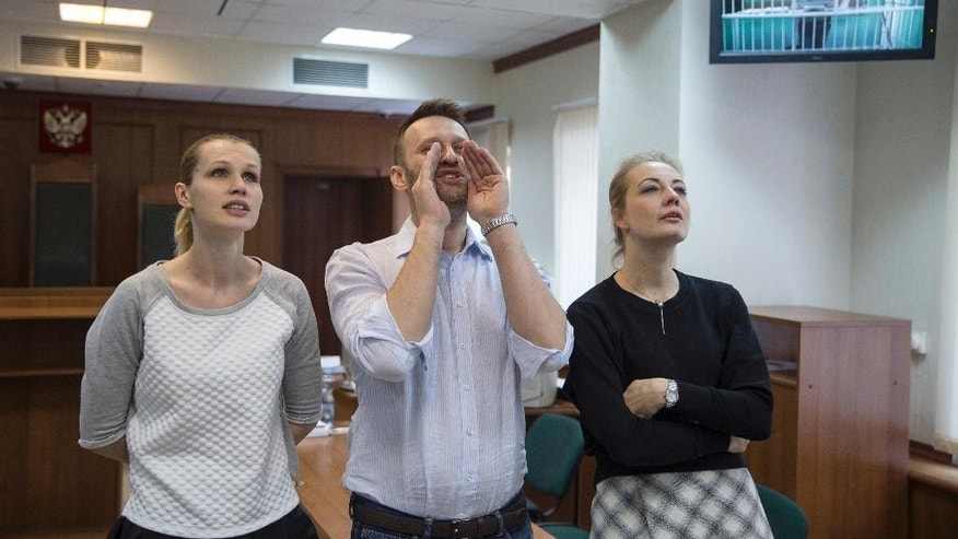 Russian opposition activist and anti-corruption crusader Alexei Navalny, center, his wife Yulia, left, and his brother Oleg's wife Victoria, right, speak to Oleg as they attend a video call with him, shown on a TV screen, at a court in Moscow, Russia, Tuesday, Feb. 17, 2015. Oleg Navalny was convicted on Dec. 30, 2014 and sentenced for three and a half years in prison. Alexei Navalny was also convicted and sentenced to the same prison term, but it was suspended. (AP Photo/Pavel Golovkin)