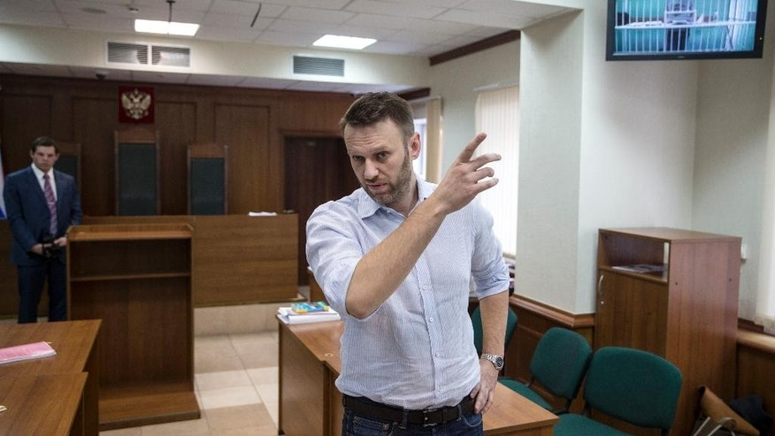 Russian opposition activist and anti-corruption crusader Alexei Navalny gestures during a video call with his brother Oleg, right shown on TV, at a court in Moscow, Russia, Tuesday, Feb. 17, 2015. Oleg Navalny was convicted on Dec. 30, 2014 and sentenced for three and a half years. Alexei Navalny was also convicted and sentenced to the same prison term, but it was suspended. (AP Photo/Pavel Golovkin)