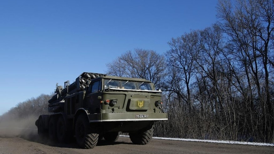 A Ukrainian army's truck with a Smerch missile launcher passes on a road stretching away from the town of Artemivsk, Ukraine, towards Debaltseve, Tuesday, Feb. 17, 2015. Ukrainian government troops and Russia-backed rebels failed Tuesday to start pulling back heavy weaponry from the front line in eastern Ukraine as a deadline passed to do so. Under a cease-fire agreement negotiated by the leaders of Ukraine, Russia, Germany and France last week, the warring sides were to begin withdrawing heavy weapons from the front line on Tuesday. (AP Photo/Petr David Josek)