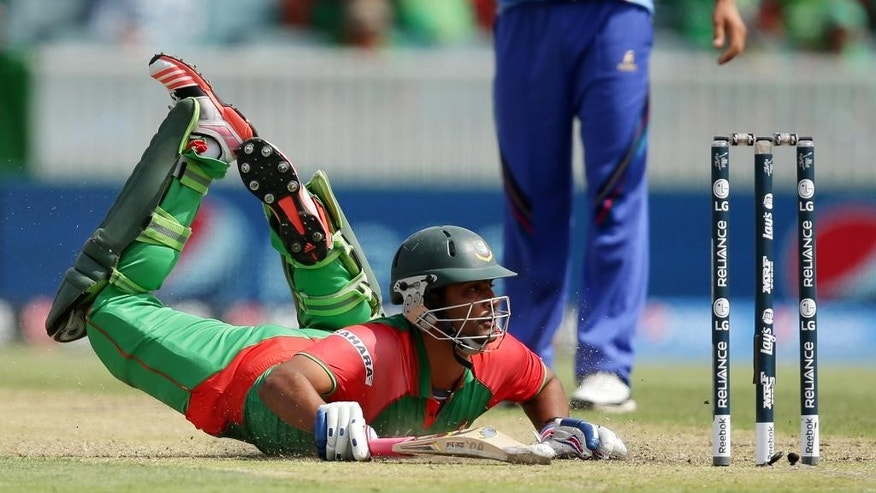 Bangladesh batsman Iqbal Tamim dives to make his ground during their Cricket World Cup Pool A match against Afghanistan in Canberra, Australia, Wednesday, Feb. 18, 2015. (AP Photo/Rob Griffith)