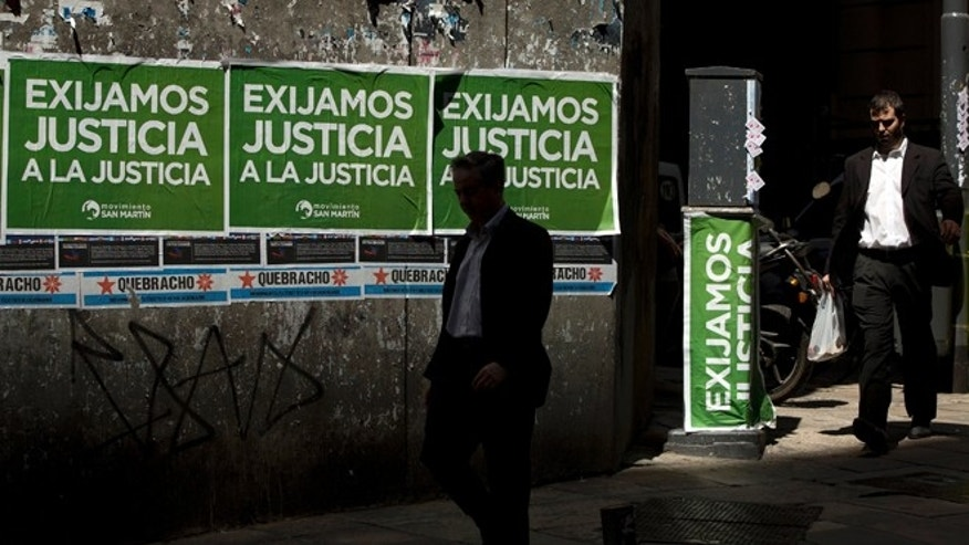 "Men walk pass posters that read in Spanish ""Demand justice to justice"", in reference to march organized by federal prosecutors demanding justice after the death of special prosecutor Alberto Nisman almost a month ago, in Buenos Aires, Argentina, Friday, Feb. 13, 2015. Nisman accused President Cristina Fernandez, Foreign Minister Hector Timerman and others in her administration of brokering the cover-up in the bombing of a Jewish community center in exchange for favorable deals on oil and other goods from Iran. Fernandez and Timerman have strongly denied the accusations, and Iran has repeatedly denied involvement in the bombing, which killed 85 people. (AP Photo/Rodrigo Abd)"