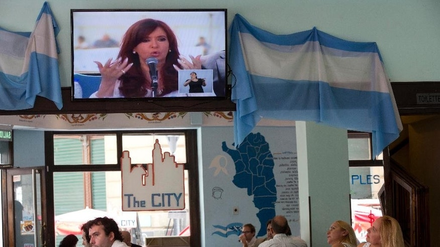 A TV shows a live image of Argentina's President Cristina Fernandez speaking at the Atucha nuclear power plant, as people eat inside a restaurant in Buenos Aires, Argentina, Wednesday, Feb. 18, 2015. The Argentine government's executive branch criticized the country's Justice Department on Wednesday, the latest verbal barb ahead of a protest being organized by investigating attorneys demanding answers in the mysterious death of prosecutor Alberto Nisman. (AP Photo/Rodrigo Abd)