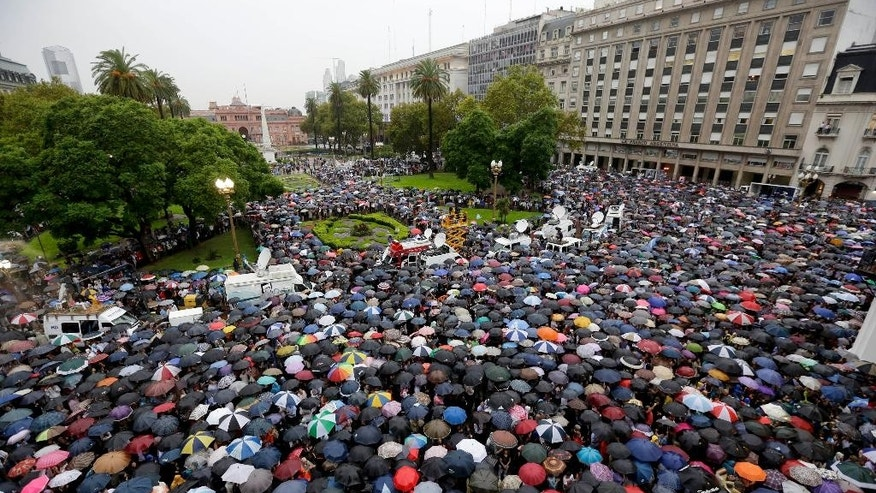 People gather in the iconic Plaza de Mayo to demand answers from the government in the mysterious death of prosecutor Alberto Nisman one month ago in Buenos Aires, Argentina, Wednesday, Feb. 18, 2015. Nisman was found dead of a gunshot wound Jan. 18, hours before he was to detail to Congress his explosive accusations that President Cristina Fernandez and top administration officials orchestrated a secret deal with Iran to shield officials allegedly responsible for the 1994 bombing of a Jewish community center in Buenos Aires. (AP Photo/Victor R. Caivano)