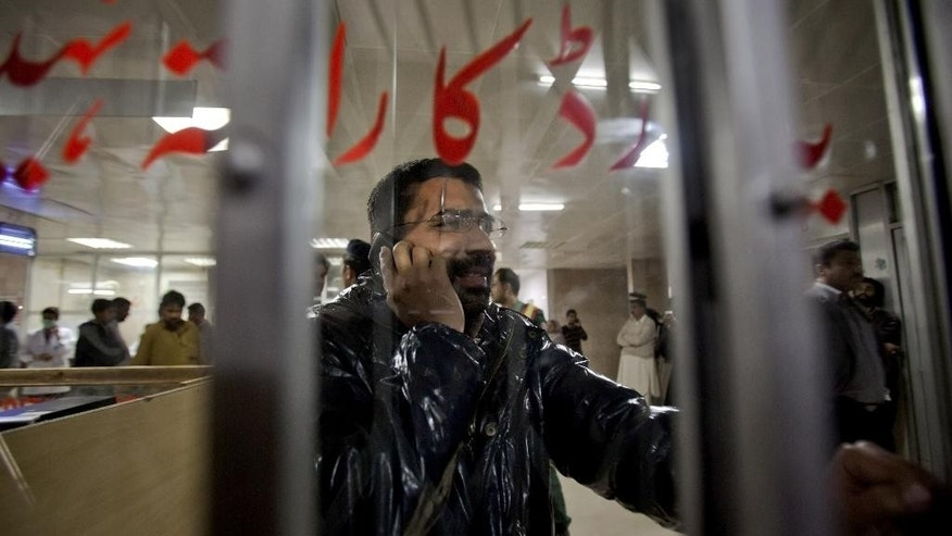 A Pakistani journalist mourns over his father's death from an attack on a Shiite mosque, at a local hospital in Islamabad, Pakistan, Wednesday, Feb. 18, 2015. Score of people were killed in an attack Wednesday evening on a mosque in Pakistan's capital belonging to the Shiite Muslim community, in the latest act of violence to target the religious minority. (AP Photo/Anjum Naveed)