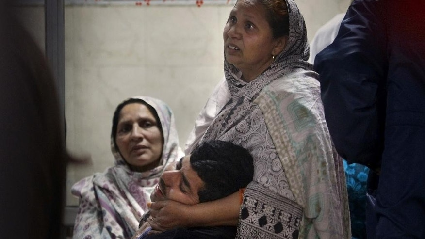 A Pakistani woman, comforts to her son as he mourns over his father's death from an attack on a Shiite mosque, at a local hospital in Islamabad, Pakistan, Wednesday, Feb. 18, 2015. Score of people were killed in an attack Wednesday evening on a mosque in Pakistan's capital belonging to the Shiite Muslim community, in the latest act of violence to target the religious minority. (AP Photo/Anjum Naveed)