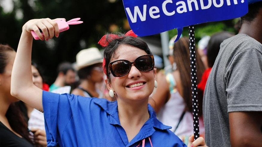 """A woman poses for photos as she attends the """"Mulheres Rodadas"""" block carnival parade in Rio de Janeiro, Brazil, Wednesday, Feb. 18, 2015. As Carnival season winds down in Brazil, hundreds of women have gathered in a large street party to mock the social stigma tied to them being sexually experienced. They called themselves """"Mulheres Rodadas"""", which loosely translates as women who have been around. (AP Photo/Silvia Izquierdo)"""