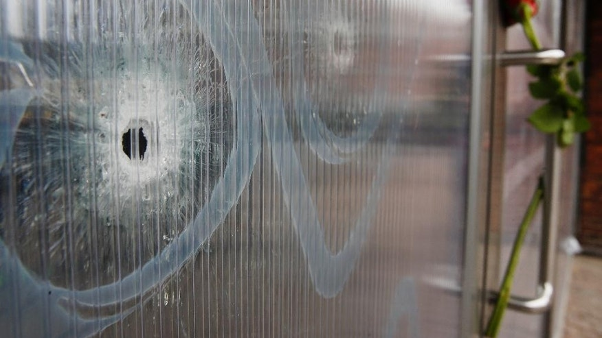 Bullet holes are seen in the window of the cultural center one of the locations of the weekend shootings in Copenhagen, Denmark, Tuesday, Feb. 17, 2015.   A Danish gunman who attacked a free-speech seminar and a synagogue was released about two weeks ago from a jail where he may have been radicalized while serving time for a vicious stabbing. As Denmark mourned the two victims, these and other troubling details emerged Monday about Omar Abdel Hamid El-Hussein's path to the country's worst terror spree in three decades.(AP Photo/Michael Probst)
