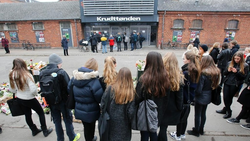 Young people take a look at the cultural center one of the locations of the weekend attacks in Copenhagen, Denmark, Tuesday, Feb. 17, 2015.  A Danish gunman who attacked a free-speech seminar and a synagogue was released about two weeks ago from a jail where he may have been radicalized while serving time for a vicious stabbing. As Denmark mourned the two victims, these and other troubling details emerged Monday about Omar Abdel Hamid El-Hussein's path to the country's worst terror spree in three decades. (AP Photo/Michael Probst)